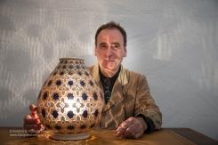 Francesco Fasano vicino ad una lampada di sua creazione